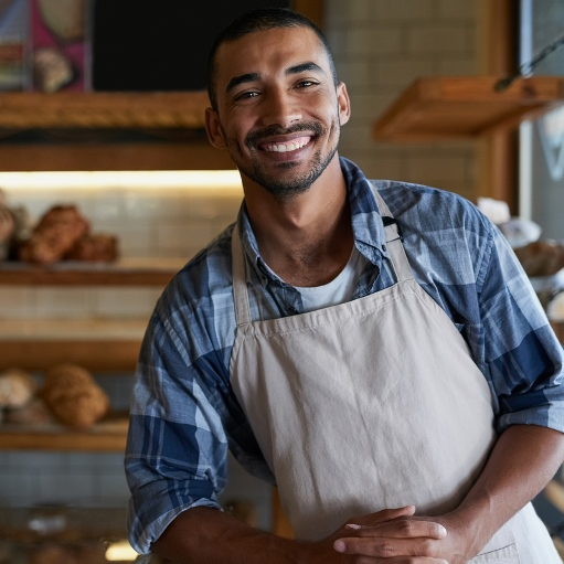 Smiling male bakery shop worker